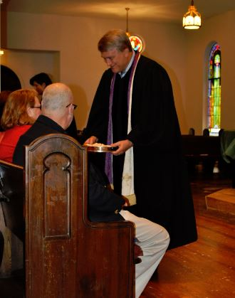 Dr. Dan serving communion to elders